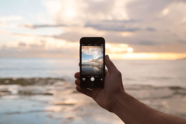 person taking photo with phone as example of mobile experience for customers