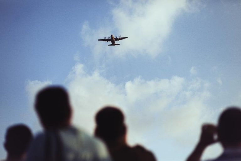 people looking up at airplane