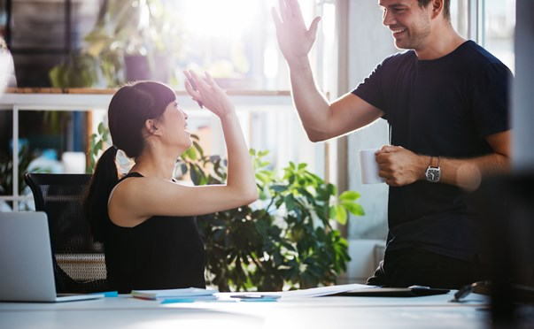 colleagues high fiving in office