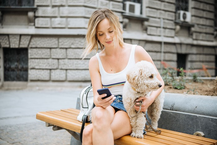 woman holding pet dog and texting