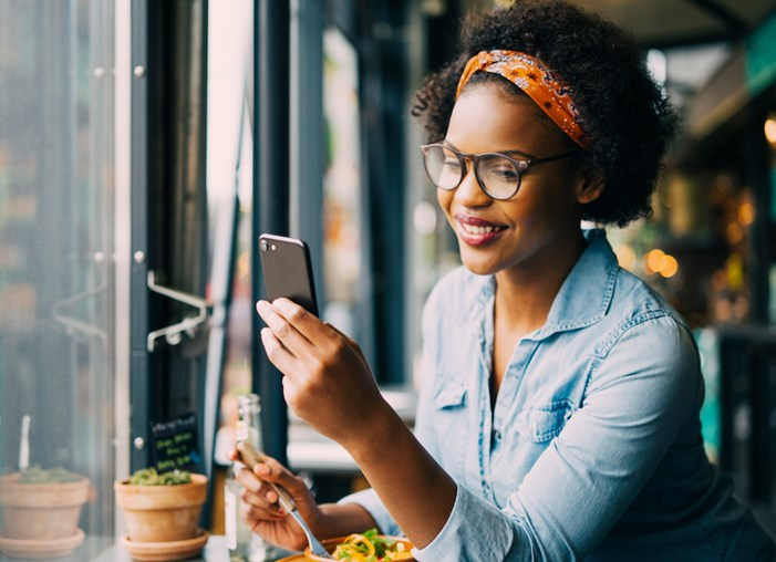 woman eating while looking at phone in restaurant
