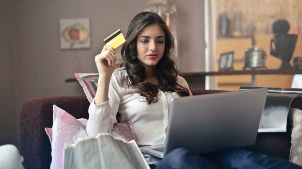 Person holding credit card using laptop
