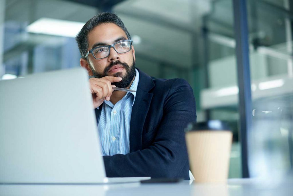 Man on computer thinking about COVID return to work