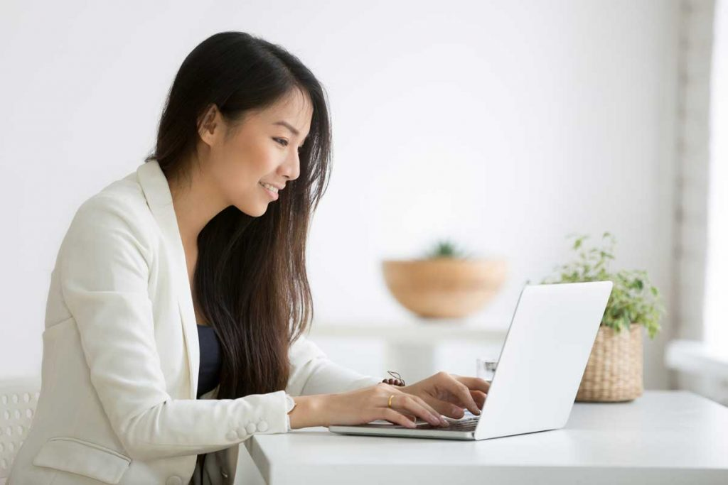 professional woman working on laptop creating customer service response templates