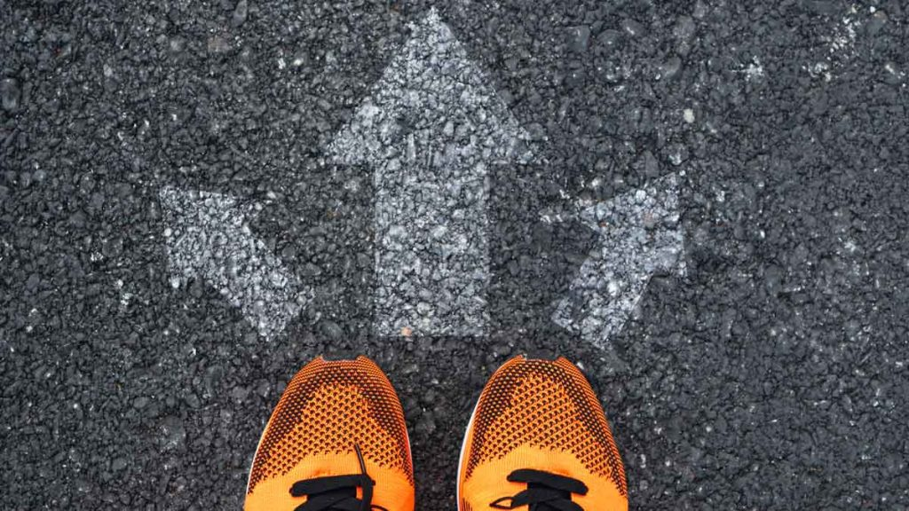 Running shoes next to arrows